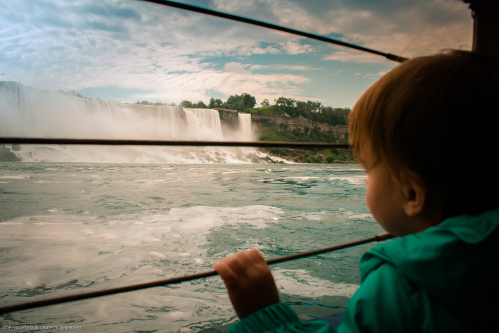Toddler looks out at Niagara Falls from aboard a boat