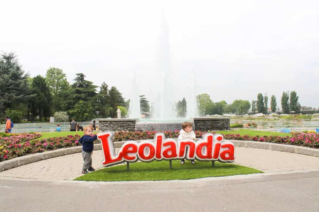 "Twin toddlers stand next t the ""Leolandia"" sign. I day trip from Milan with kids"