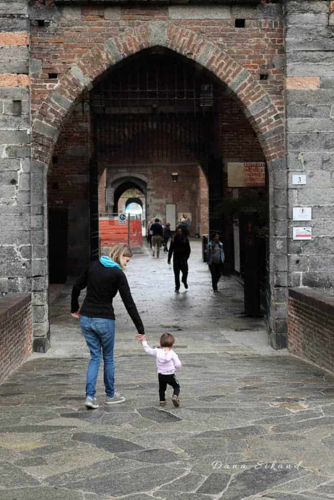 Mother walking through the drawbridge of the Sforza Castle in Milan Italy with a toddler. Things to do in Milan.