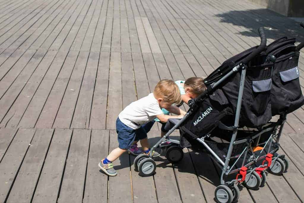 Twin toddlers push Macalren twin triumph buggy around a boardwalk