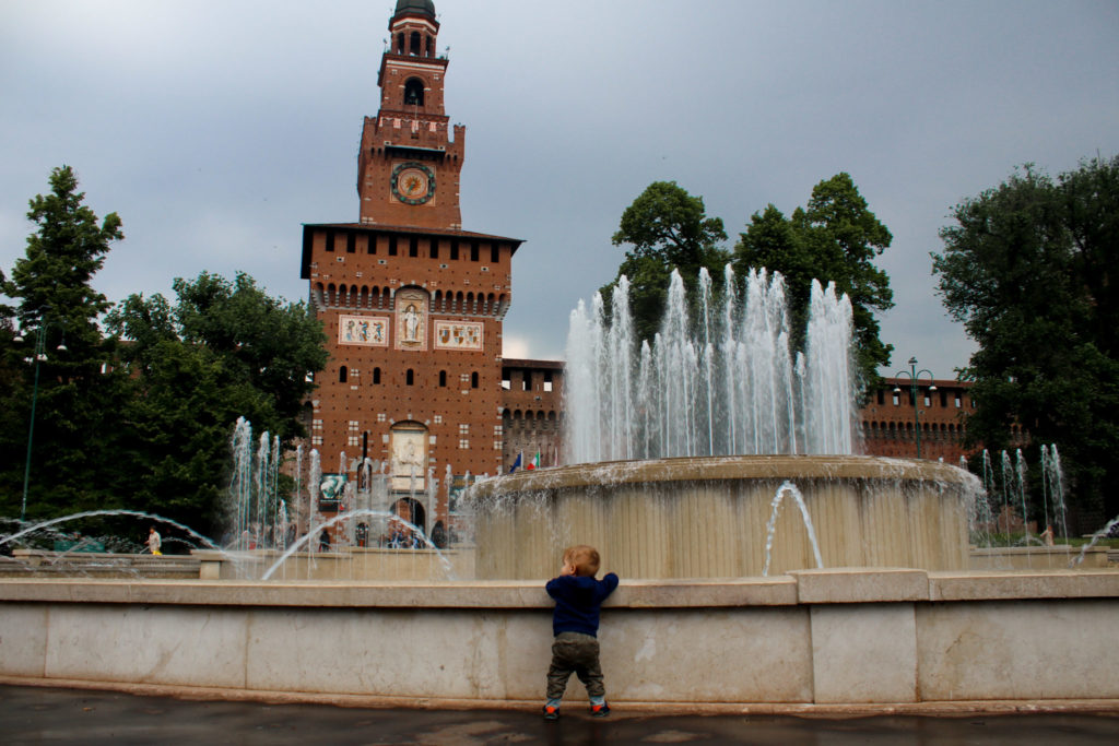 Boy looks at huge fountain in Milan