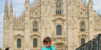 Toddler in Milan rubs her sleepy eyes .