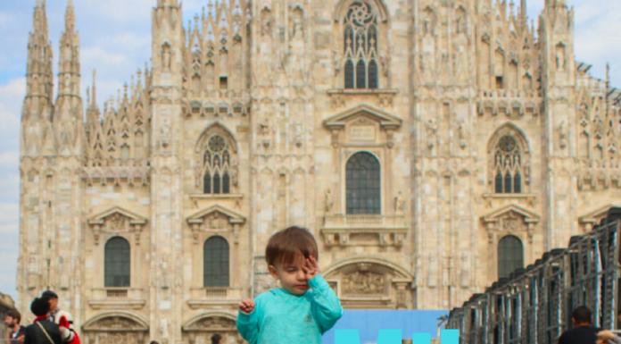 Toddler in Milan rubs her sleepy eyes .