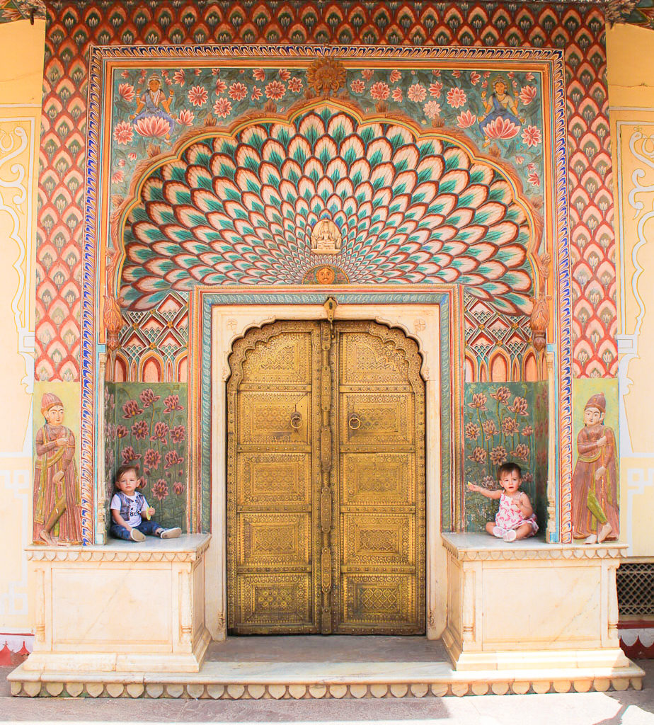 Toddlers sit ina colourful door way in the pink city Jaipur, India. Things to do in Jaipur.