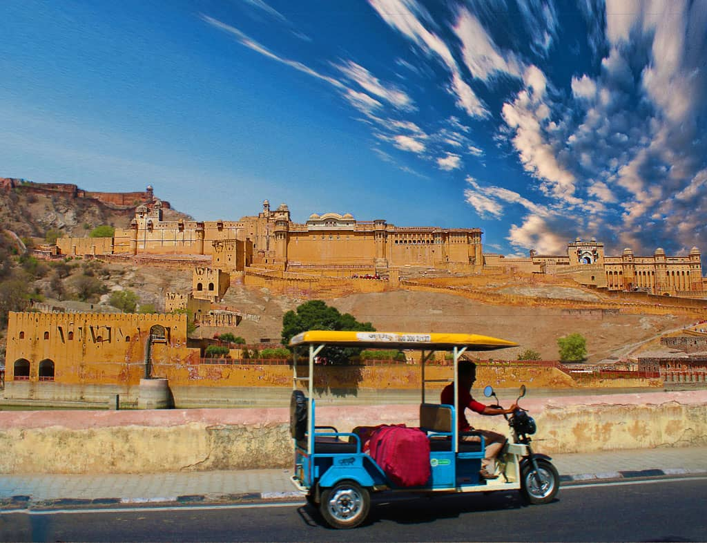 A tuk tuk taxi passes in front of Amer Fort - Jaipur Attractions.