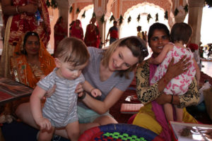 Toddler sits with locals and admires their art in the City Place of Jaipur. Jaipur with Kids.