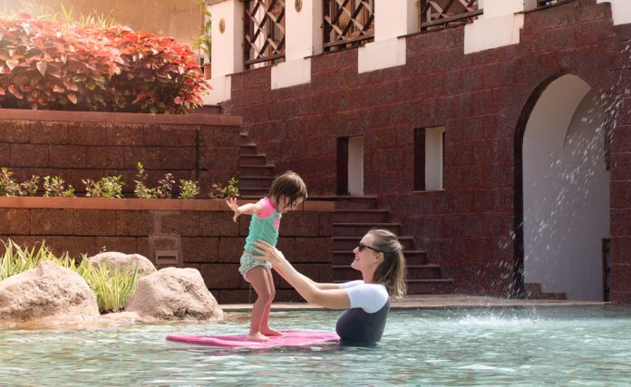 Mother helps daughter balance on a body board in a pool while on vacation