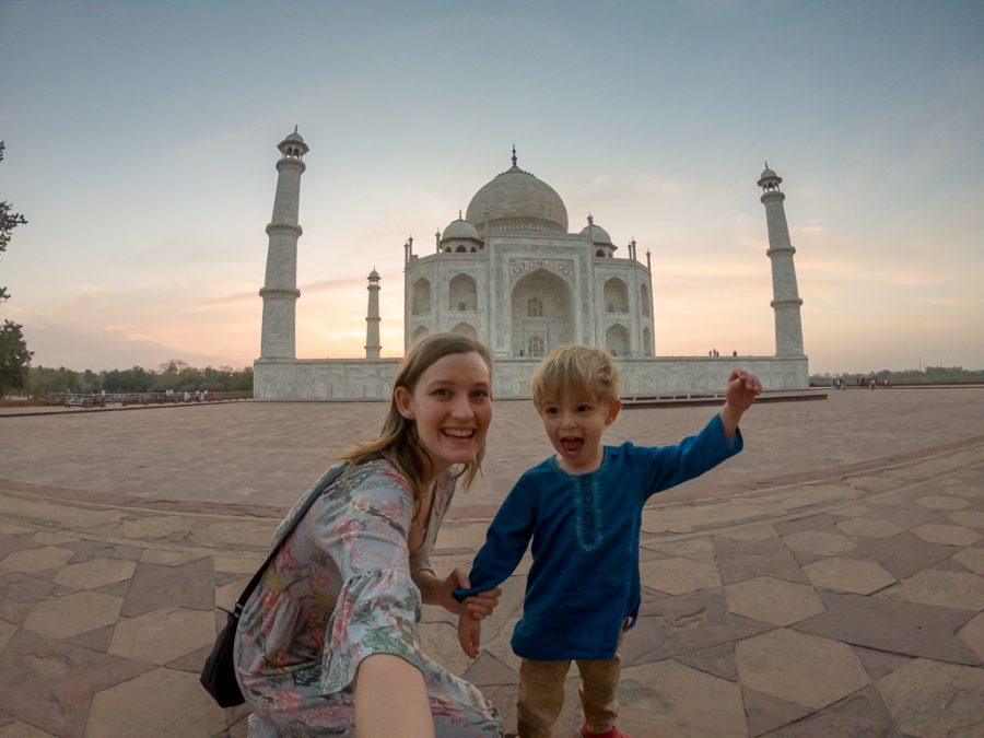 Mother and toddler son pose in front of the Taj Mahal while on a family vacation.