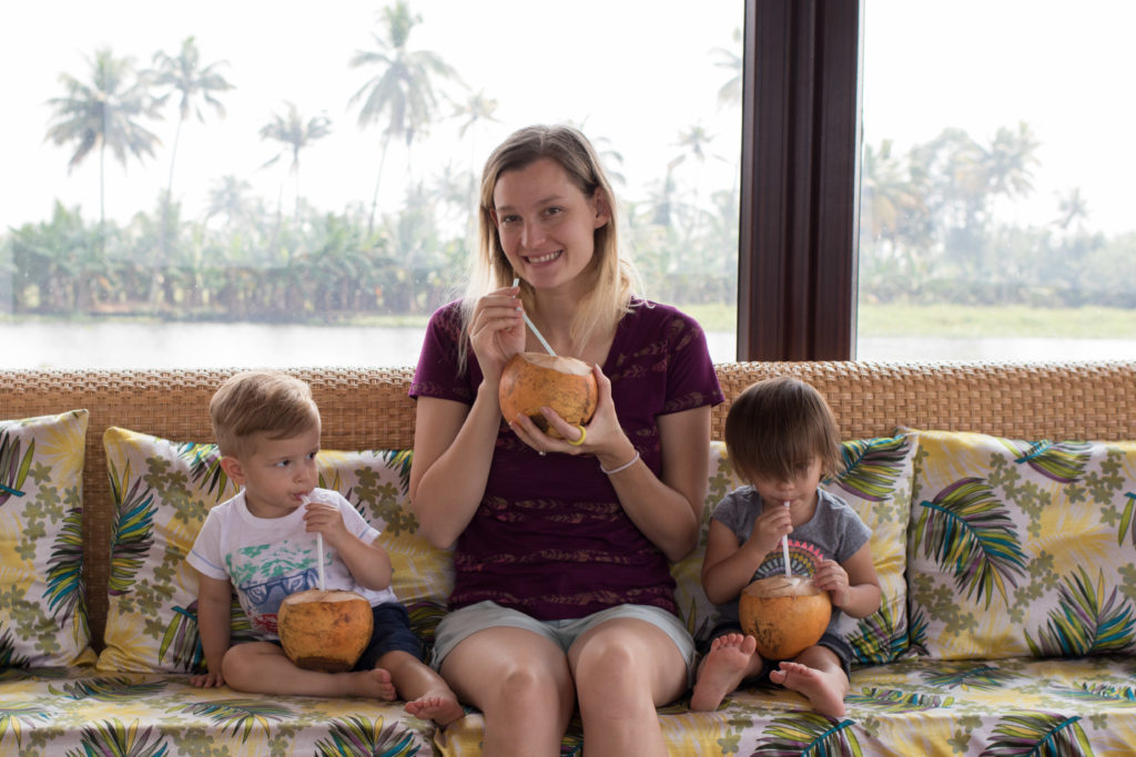 Small family enjoying coconut water on board a houseboat in Kerala