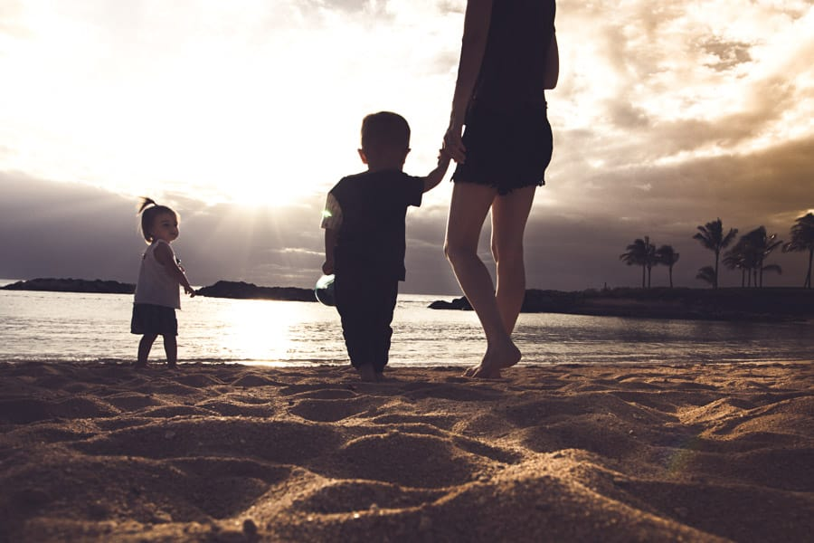 Mother holds a toddlers hand and walks along the shoreline of the Ko Olina Lagoons
