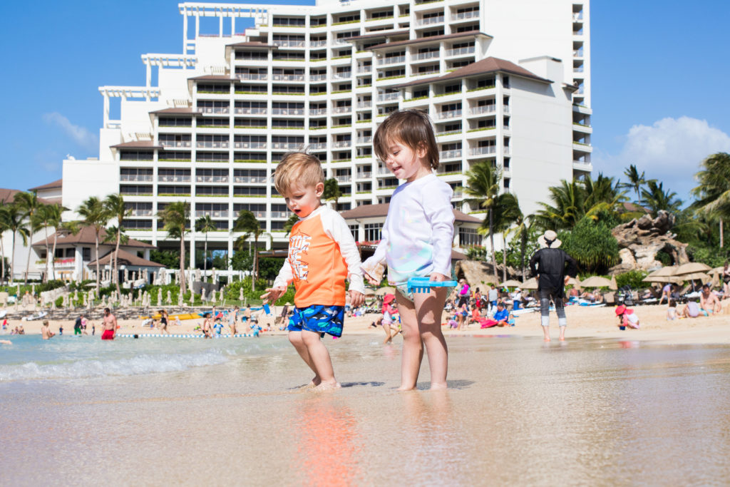 Two toddler enjoy the shoreline at the Four Seasons KoOlina