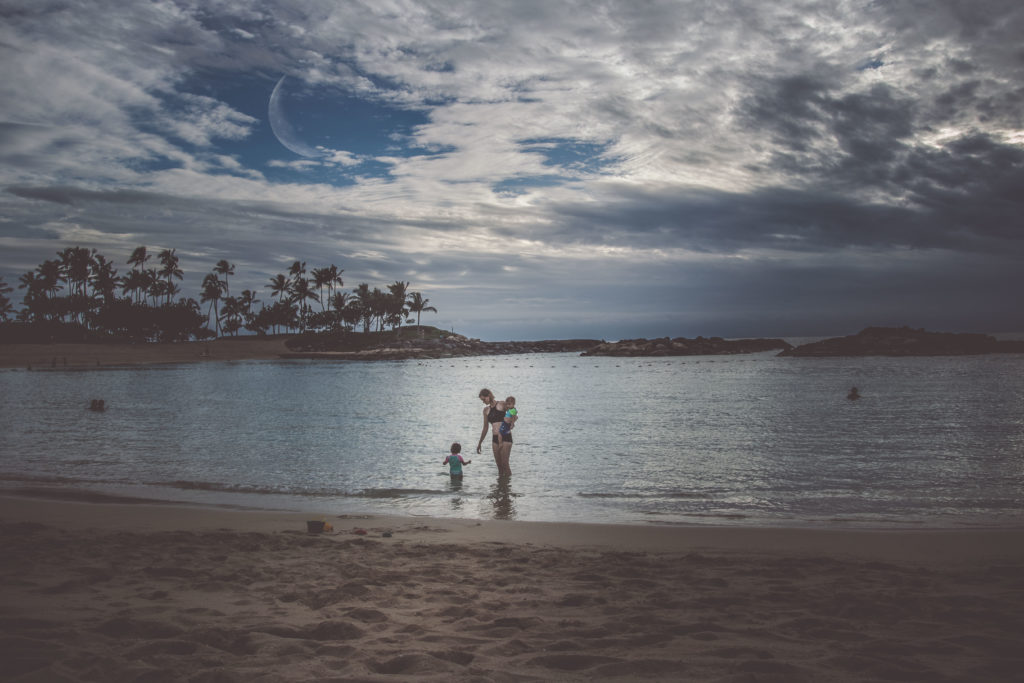 Mother walks with her twins in Ko Olina Beach park