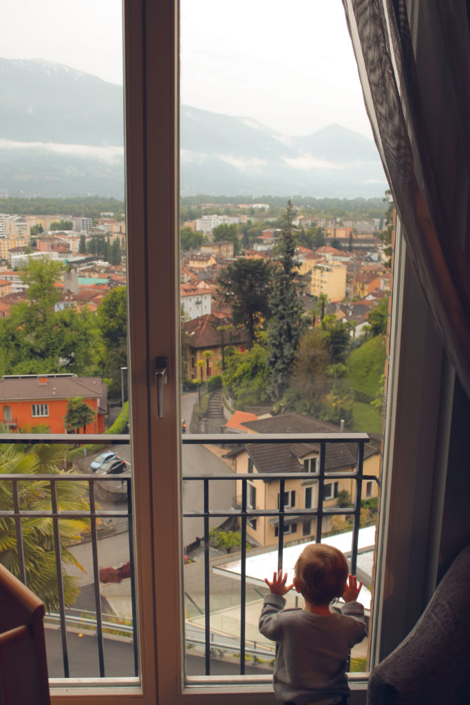 Toddler looks out of the hotel window to see the lake and Swiss alps. He Loved this family vacation.