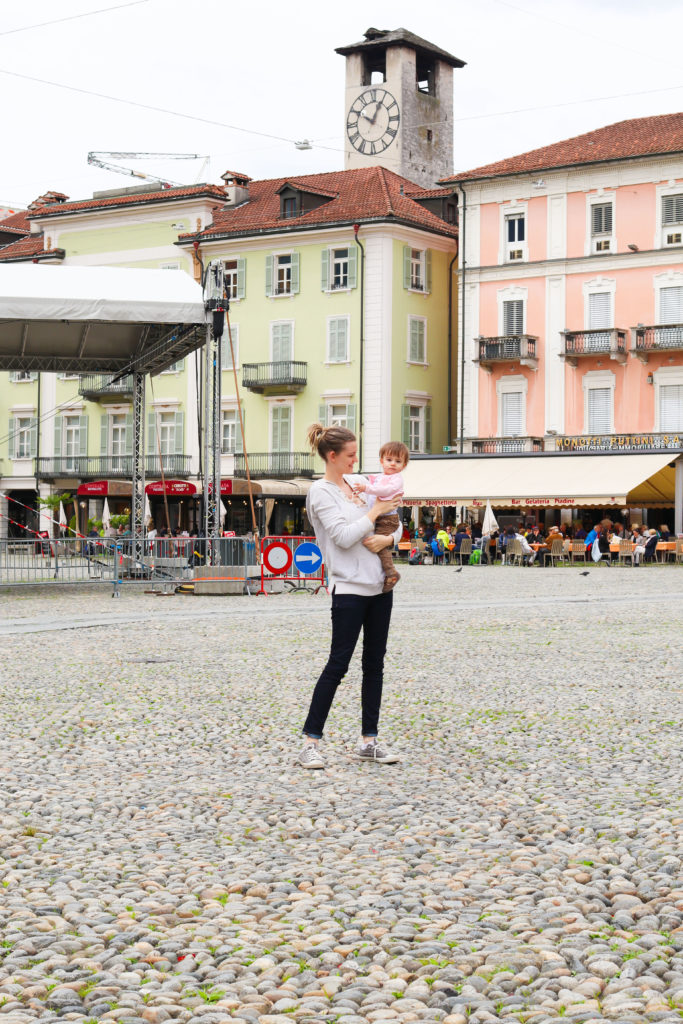 Mom holds baby in the middle of the Piazza Grande during vacation.