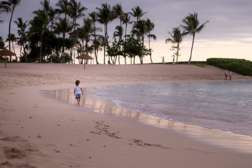 Toddler walks along a Ko Olina lagoon in hawaii at sunset