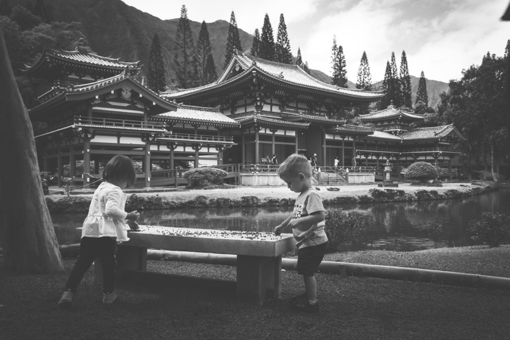 Two toddlers play in front of Byodo-In Temple in Kaneohe, Haawaii