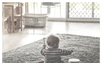 Image of baby sitting in childproofed room.
