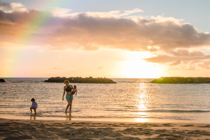 Mother walks along shoreline at sunset with twin toddlers in Hawaii