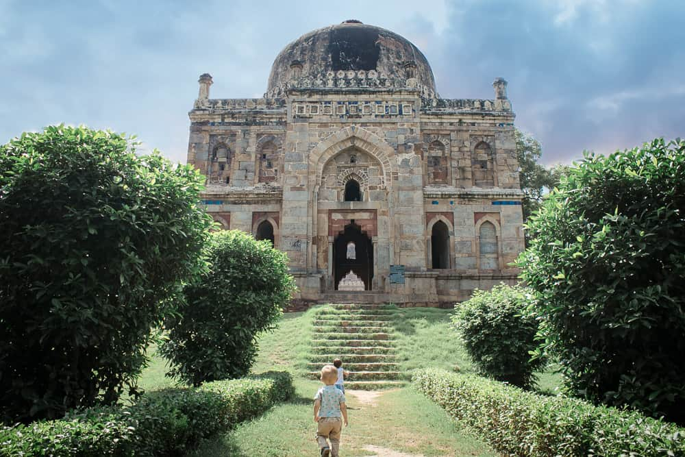 Two toddlers walk towards a giant historical monument in Lodhi Gardens. Fun parks in Delhi.