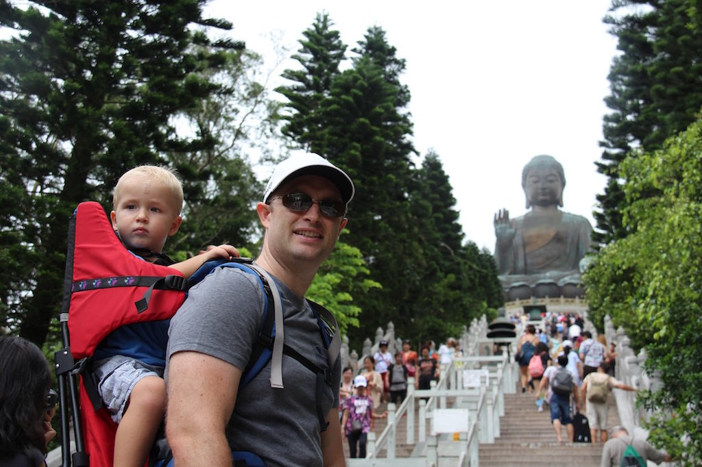 Father wears a baby on his back as he hikes up to big Buddha in Hong Kong. Places to go with toddlers.