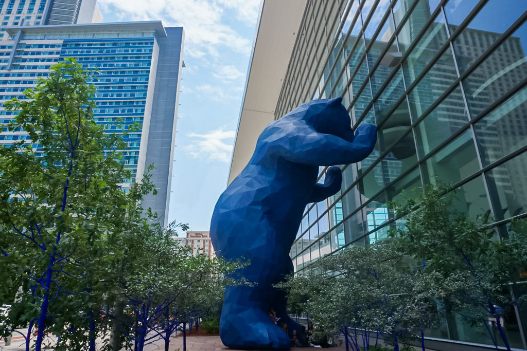 A giant blue bear looks into a building window. Denver is one of the best places for kids to visit.