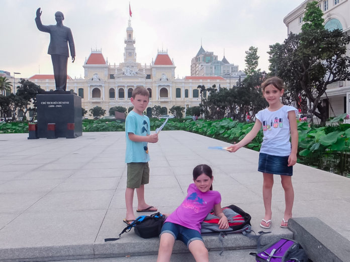 Three kids having fun in a public square. Fresh influenced architecture can be seen in the distance.