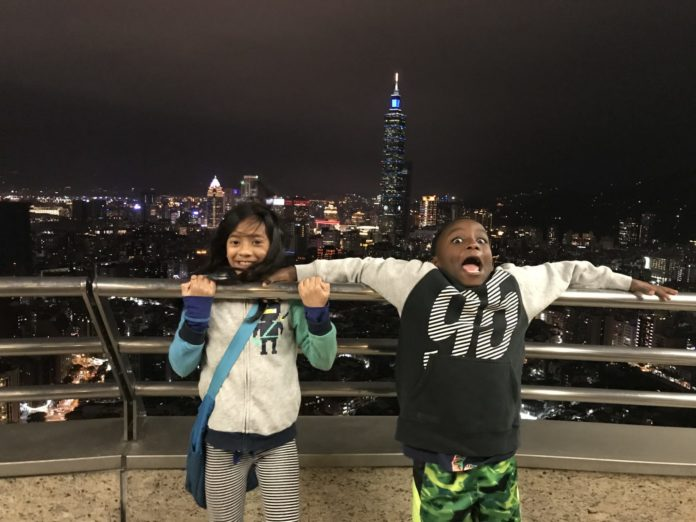 Two excited children have fun on the balcony of a skyscraper.