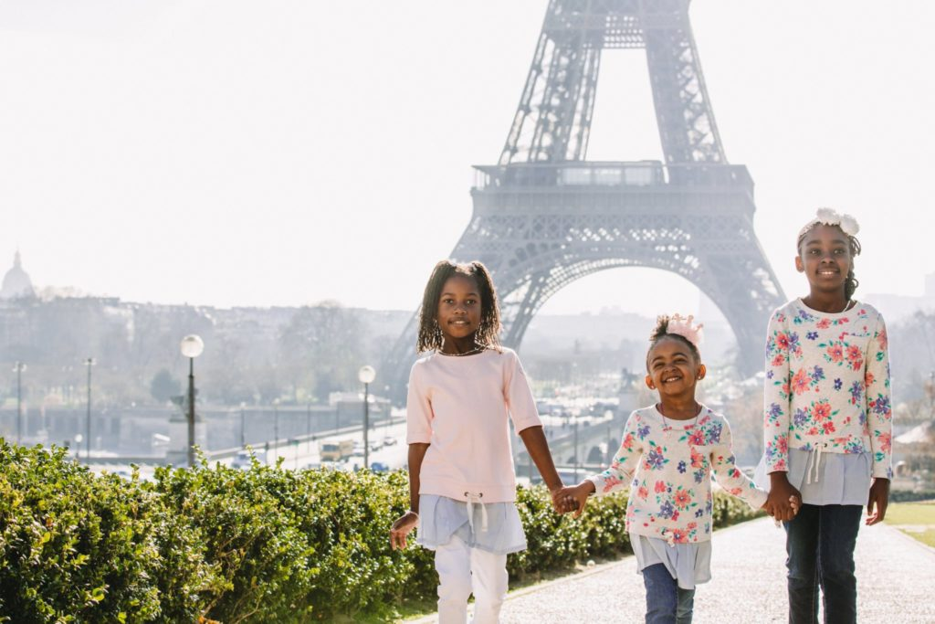 Three kids pose in front of the Eiffel Tower in Paris a premier tourist attraction with kids. Paris is a great place to take kids.