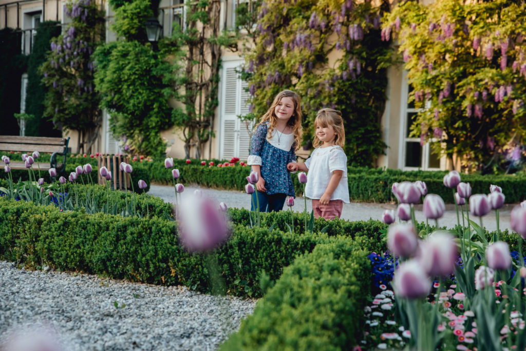 Two children enjoy the spring flowers in Salzburg, Austria. Best places for kids to visit.