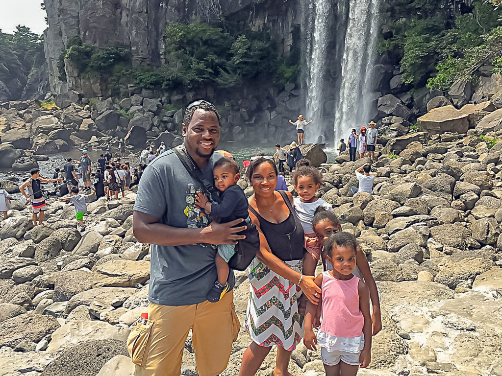 Family of 5 stands in front of a large waterfall on juju island - tourist attractions with kids.