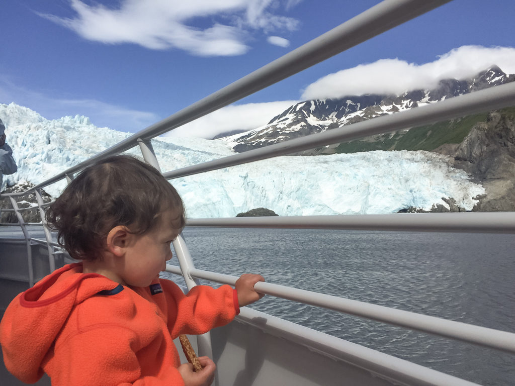 Toddler holds onto railing and takes in the ice capped view in Seward, Alaska