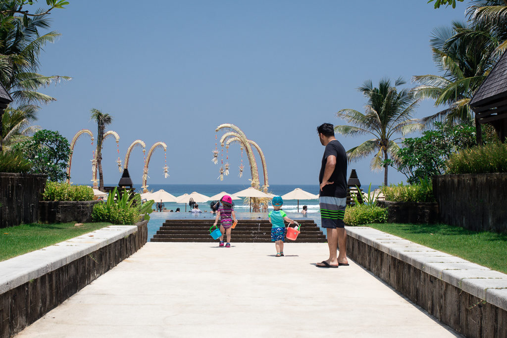 Two kids walk towards the Ritz Carlton Bali pool