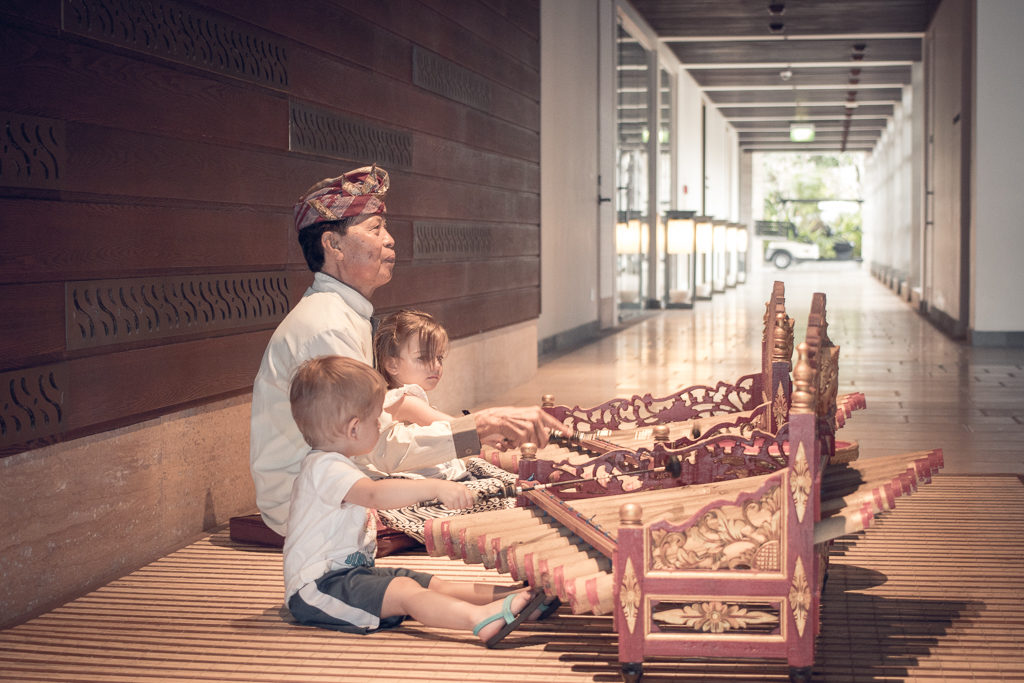 twin toddlers sit and play a gamelan in Bali
