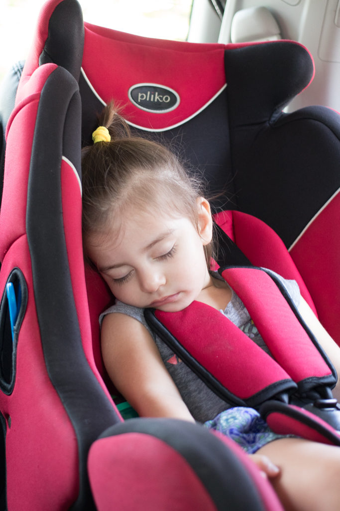 Toddler sleeps in a carseat provided by the Ritz Carlton Bali