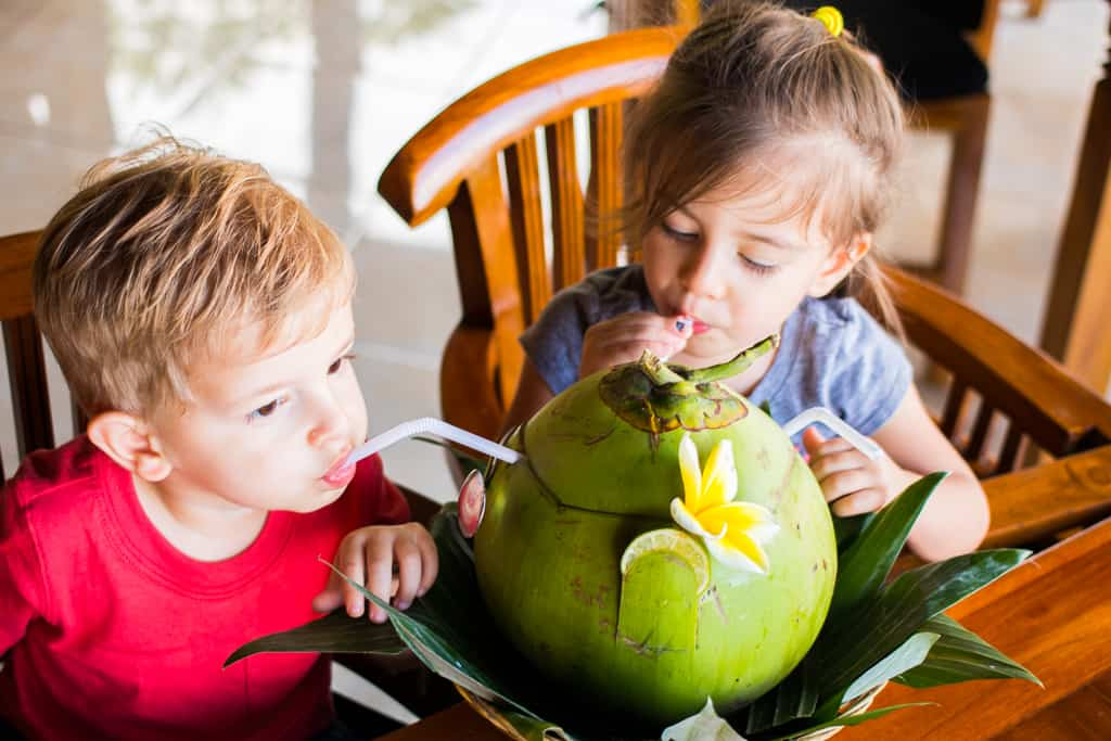 Toddlers drink from a coconut