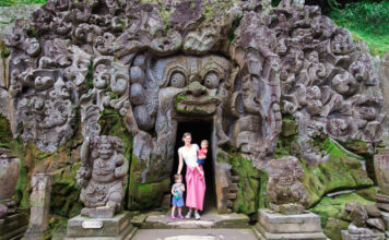 Mother stands in doorway of a temple in Ubud with twin toddlers