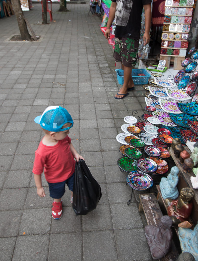 Toddler looks for handi crafts in a Bali market. Bali with kids.