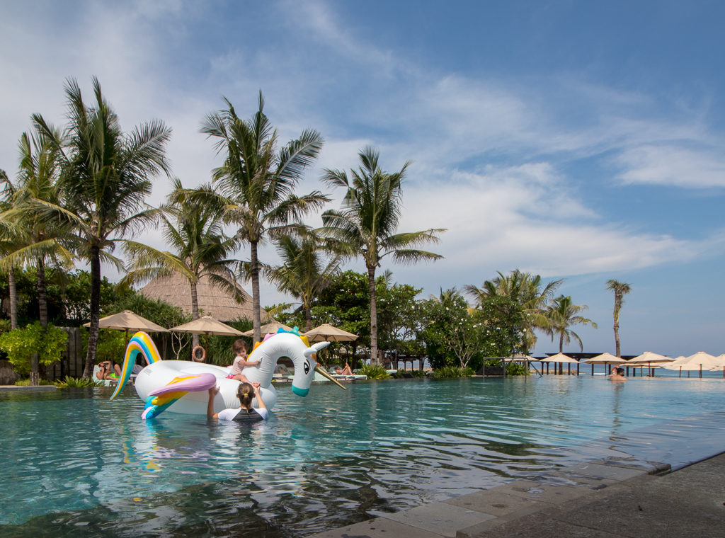 Toddler floats on a giant unicorn floaty in a pool at the Ritz Carlton Bali. Bali hotels with kids clubs.