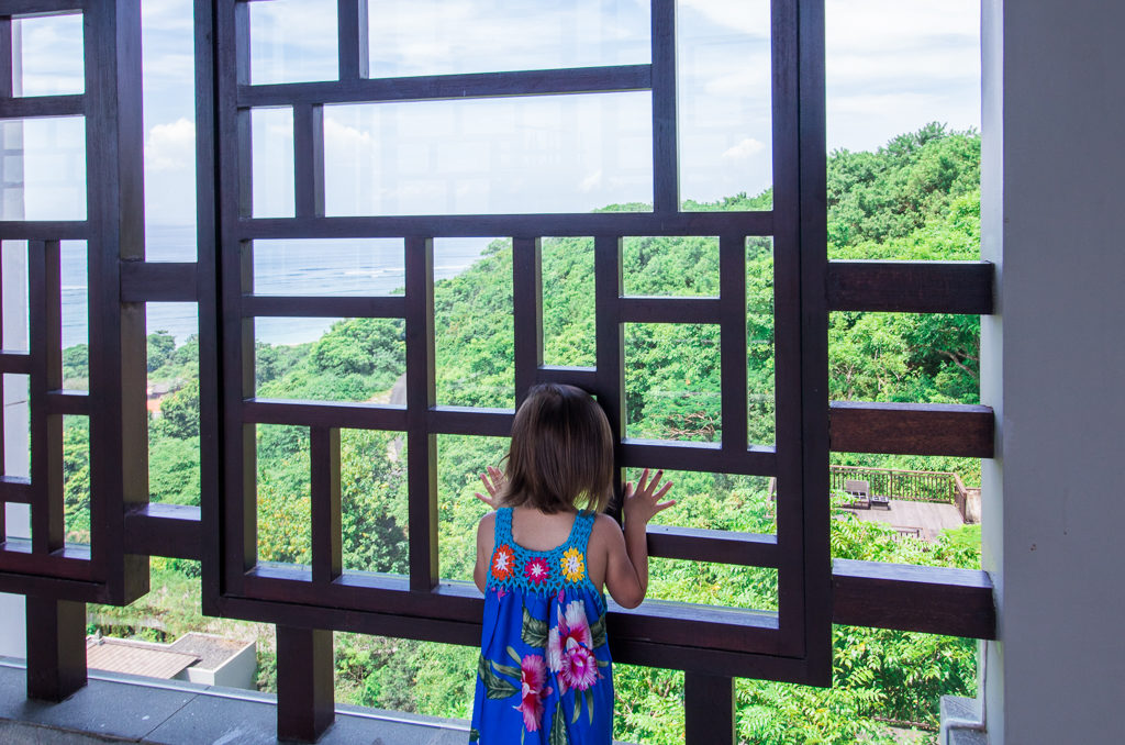Toddler stares out of the window at the beautiful Bali shoreline