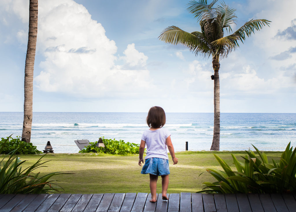 Toddler walks towards the ocean in Nusa Dua, Bali