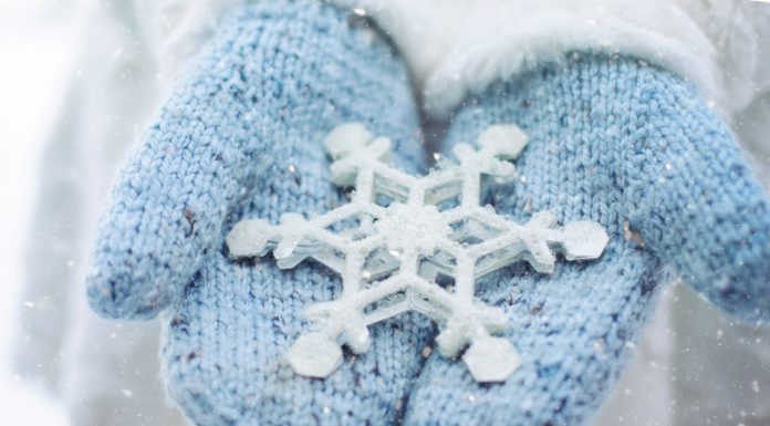 Pair of mittens holding an oversized snowflake
