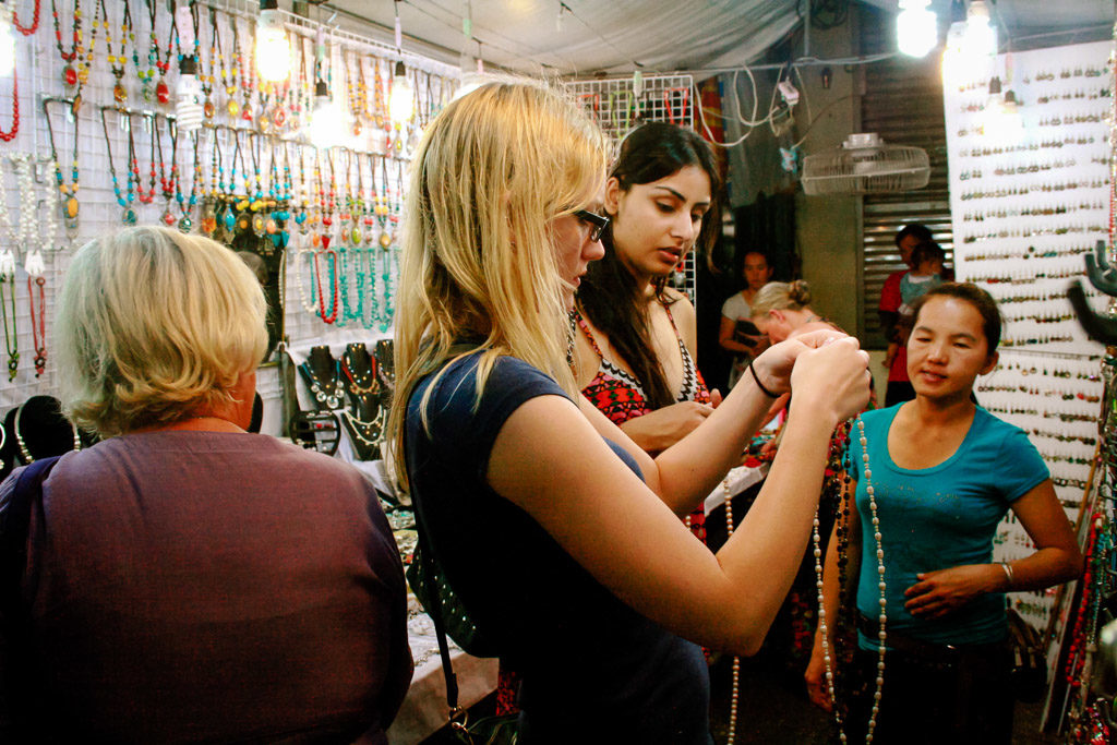 Two women buy freshwater pearls in a Thailand night market. This was my first experience learning how to haggle.