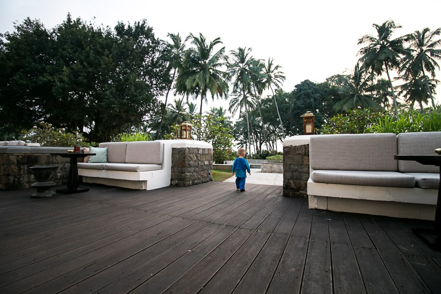 Toddler walks on hotel grounds in Goa India.