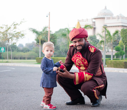 Indian man kneels next to a toddler in India