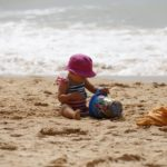 Baby plays in the sand in a secluded beach on Oahu, Hawaii