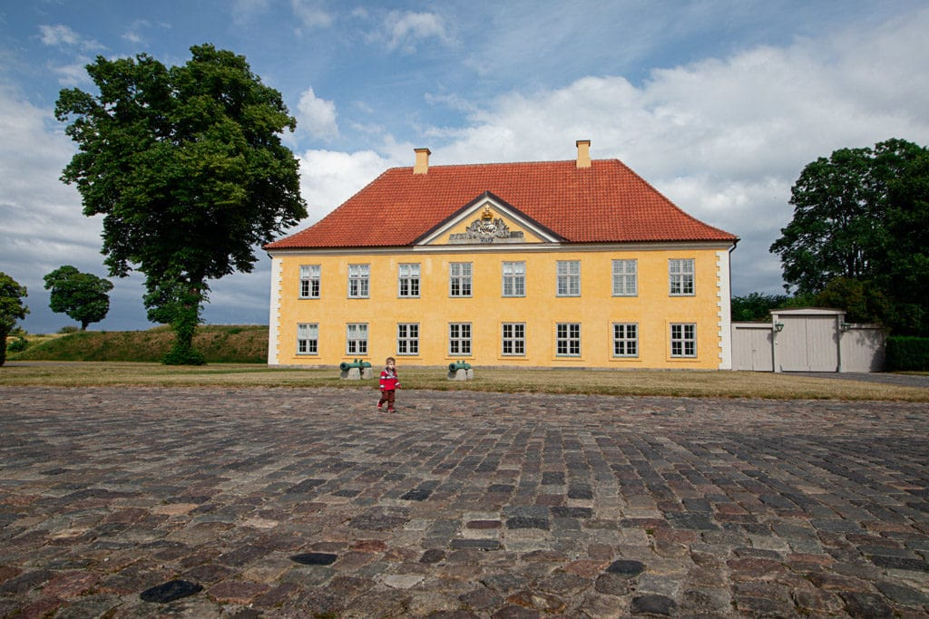 Toddler wanders around kastellet with large, yellow house in the background