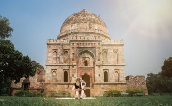 What to wear in India. Woamn sits in front of large monument in New Delhi