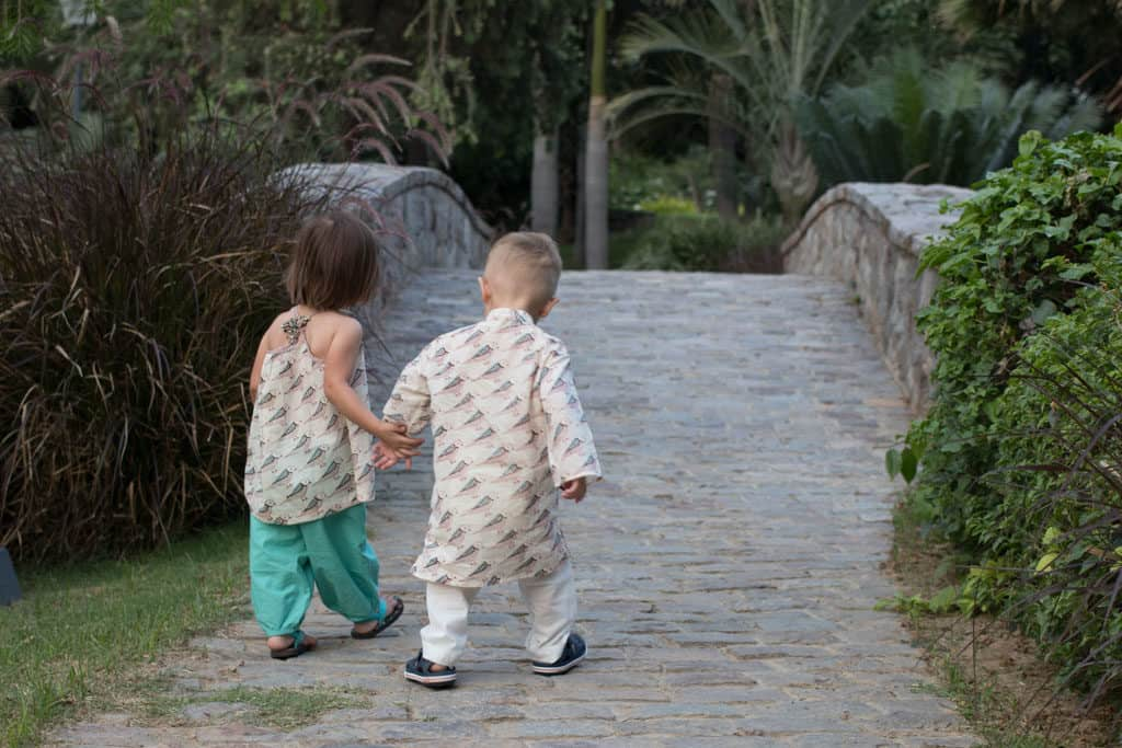 Twin toddlers walk hand in hand wearing coordinating Indian clothing