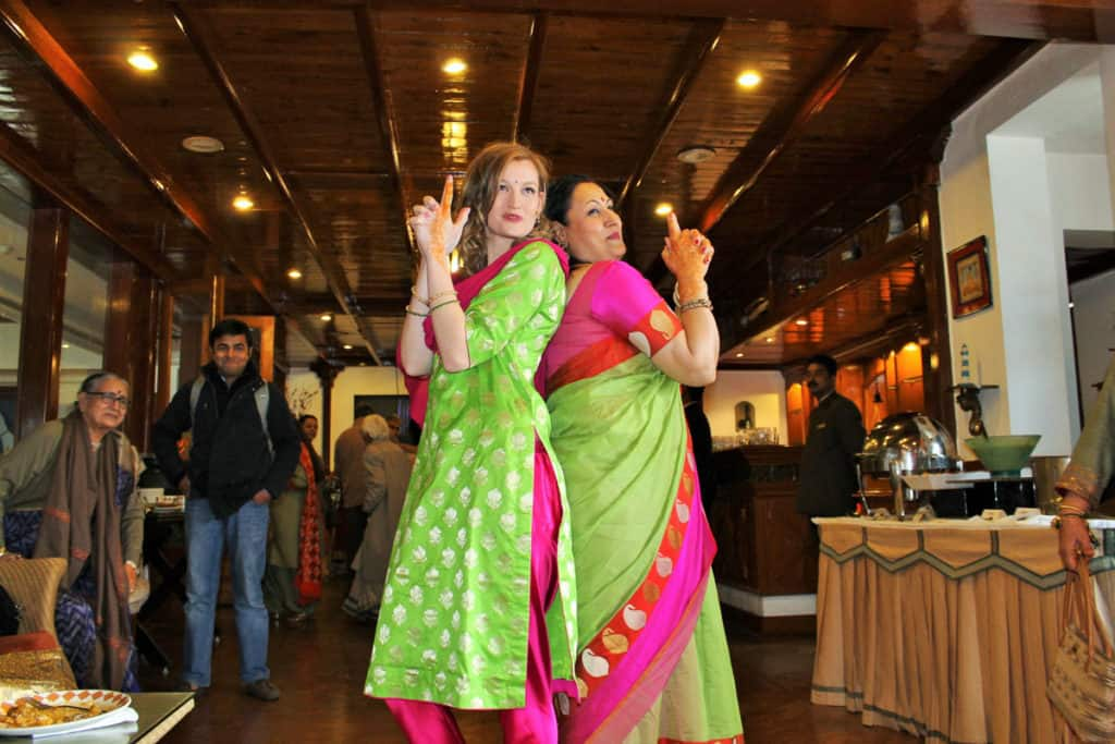 Two women pose at a wedding in India.