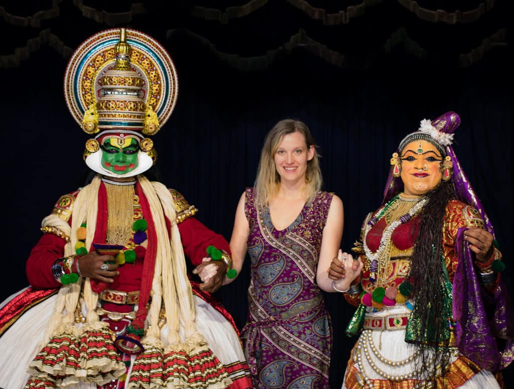 oman stands between two performers in Kerala
